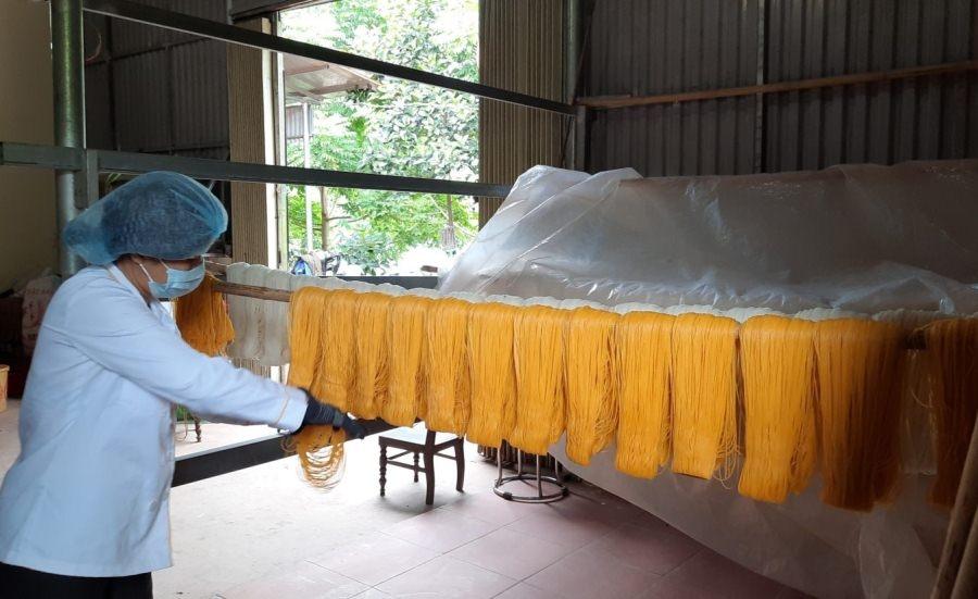 Chủ cơ sở Bún ngô Thuận Anh (Đình Lập) treo bún lên sào sau khi tạo khuôn và cắt sợi bún với độ dài phù hợp.