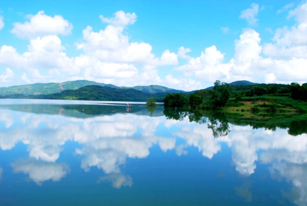 Mặt hồ trong vắt, yên bình, với những áng mây, rừng cây in bóng